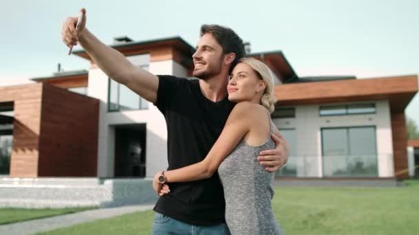 Bohatý pár se objímá v blízkosti luxusních bytů. Selfie portrét šťastného páru