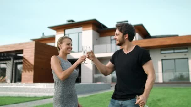 Romantic couple drinking champagne near house.