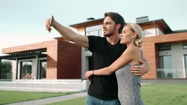 Veselý pár, který si vezme fotografii na mobilním telefonu poblíž luxusního domu.