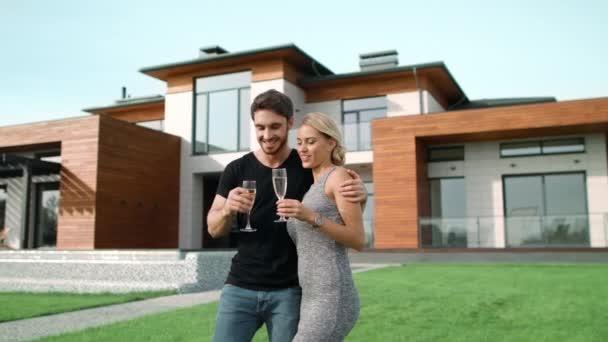 Erfolgreicher Mann und Frau trinkt Champagner vor Luxushaus.