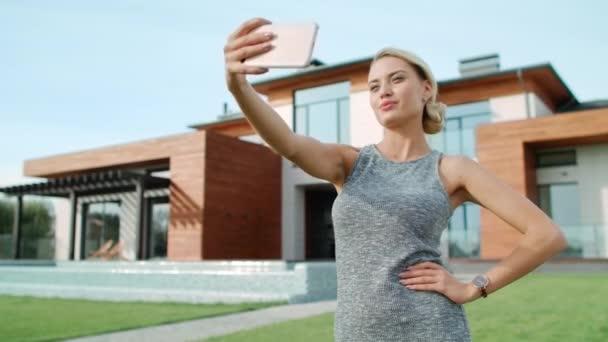 schöne Frau macht Selfie-Foto vor Luxus-Appartementhaus