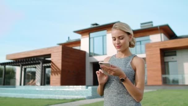 schöne Frau tippt Handy in der Nähe von Luxus-Haus außen. Erfolgreicher Lebensstil