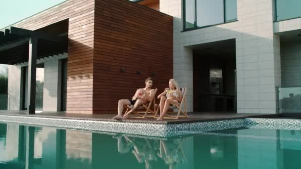 Rich couple relaxing near swimming pool atprivate house.