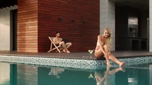 Sensual woman applying suncream on legs near pool at luxury house.