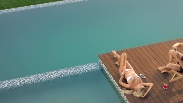 Beautiful model sunbathing on poolside with boyfriend. Strong man taking picture