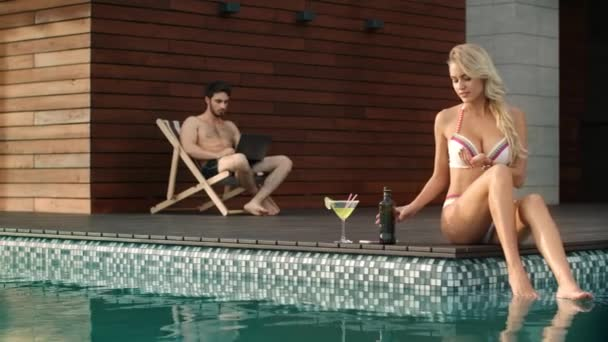 Cheerful woman moisturizing body on poolside. Happy couple resting on poolside