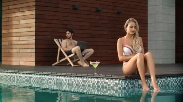 Frau befeuchtet Körper in Pool in der Nähe von Privathaus.