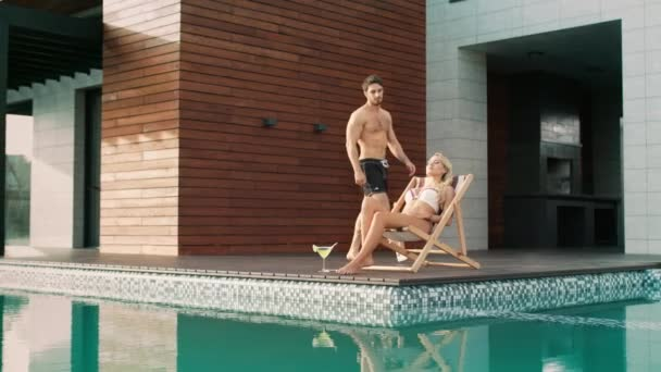 Handsome man touching woman near swimming pool at luxury house.
