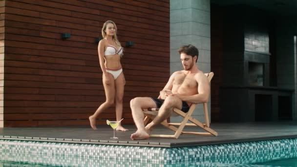 schöner Mann benutzte Handy in der Nähe von Pool in Luxus-Haus.