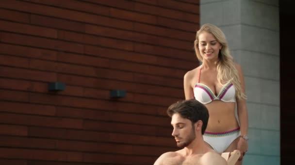 Sexy woman going to man outdoor. Closeup beautiful couple near pool