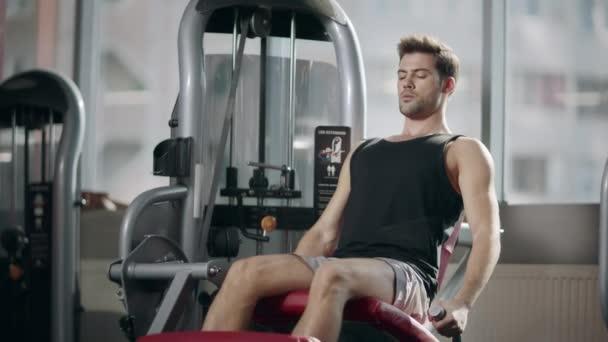 Erős sportoló csinál lábát gyakorolni sport szimulátor Fitness Club.