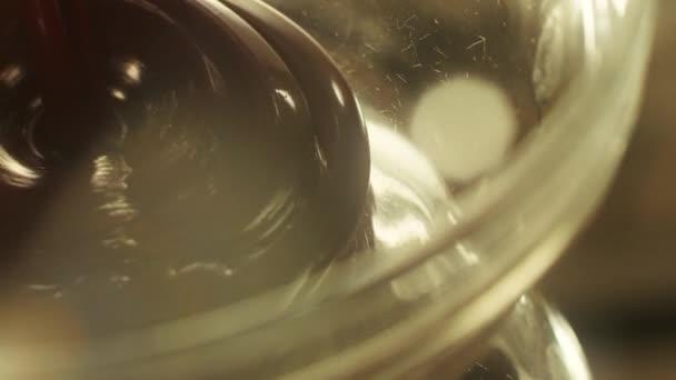 Nahaufnahme Schokoladenfondue tropft in transparenten Teller.