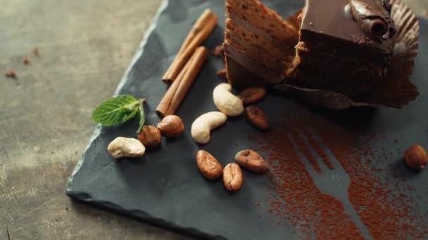 Čokoládový dort s kešu ořechy, skořicí a kakaovými boby ležícími na talíři.