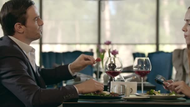 Handsome man feeding woman at romantic dinner. Couple dining at romantic date