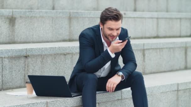 Obchodník nahrávání audio zprávy na mobilu venku.Man sedí na schodech