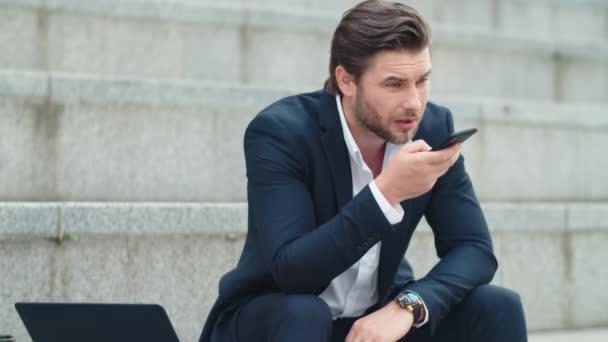 Obchodník mluví po telefonu na ulici. Muž sedící na schodech