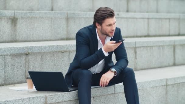 Hezký podnikatel nahrávání hlasové zprávy na mobilním telefonu v městské ulici