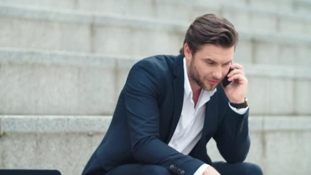 Obchodník mluví na chytrém telefonu ve městě. mužský zaměstnanec slaví vítězství
