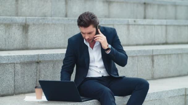 Podnikatel pracující na notebooku na ulici. Manažer mluví na smartphone