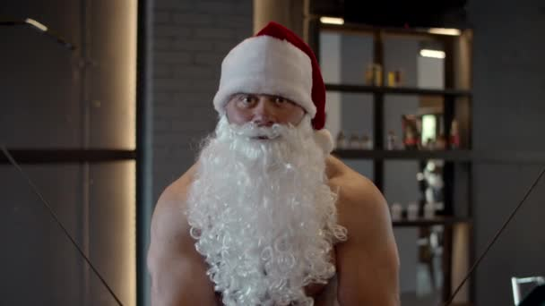 Sexy santa claus doing bicep curls in sport club. Sportsman training at gym