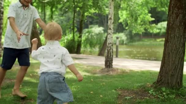 Starší bratr si hraje s batoletem v parku. Šťastná rodina s piknikem venku