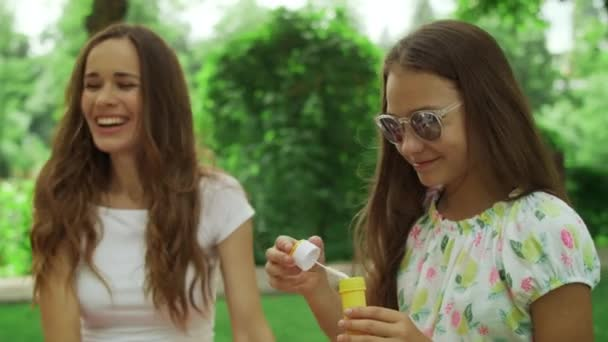 Woman and girl playing with soap bubbles in park. Family laughing outdoors