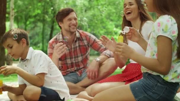Děti si hrají s mýdlovými bublinami v lese. Rodinný čas strávený spolu v parku