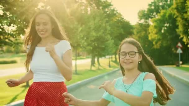 Girl and woman dancing in park. Mother and daughter gesturing with hands