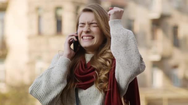 Glückliche Frau, die draußen gute Nachrichten per Telefon hört. Aufgeregtes Mädchen mit Smartphone.