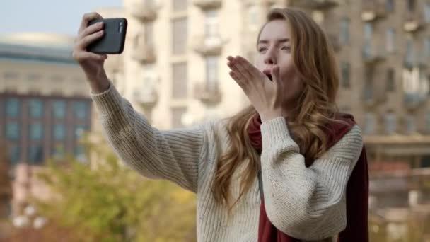 Hübsche Frau macht Selfie-Foto per Telefon. Nettes Mädchen dabei Bilder von der Kamera.