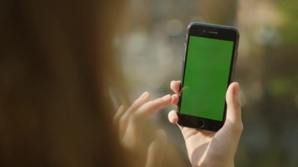Weibliche Hände mit Telefon mit grünem Bildschirm. Mädchenhände halten Handy im Freien.