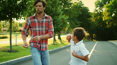 Boy and man legs dancing barefoot on street. Father and boy having fun outdoors