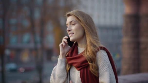 Hübsche Frau spaziert mit Handy. Fröhliches Mädchen, das im Freien telefoniert.