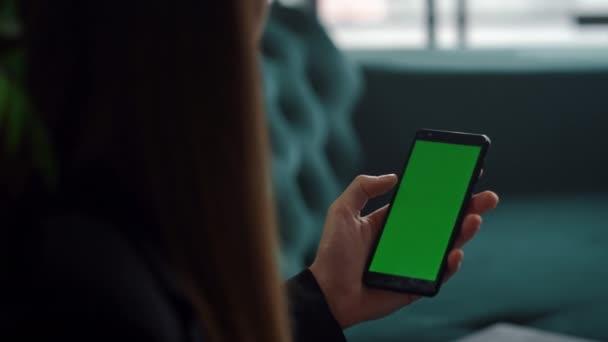 Frauenhände mit Smartphone mit grünem Bildschirm. Unbekanntes Mädchen telefoniert