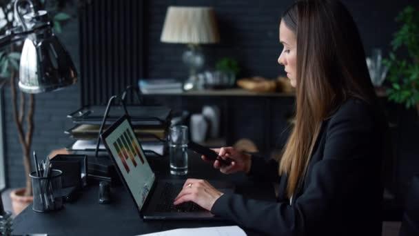 Podnikatelka pracující na laptopu v kanceláři. Zaměstnanec používající smartphone