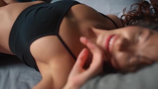 Leidenschaftliche Dame spielt mit sich selbst im Bett. Sexy Dessous Mädchen berührt Lippen
