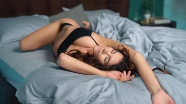 Sensual woman basking on bed. Perfect girl opening eyes in luxury bedroom.