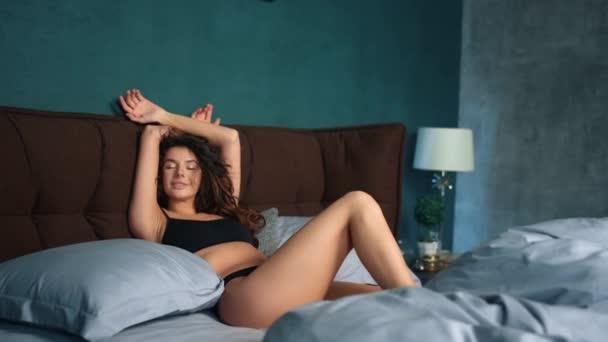 Sexy žena ležící mezi polštáři v posteli. Krásná dívka relaxační v ložnici.