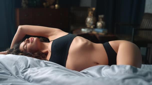 Štíhlá holka se doma natahuje na posteli. Přírodní krása žena relaxační v ložnici