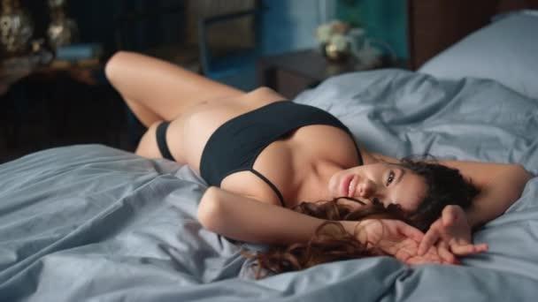 Szexi lány fekszik az ágyon. Csábító lány néz kamera a hálószobában