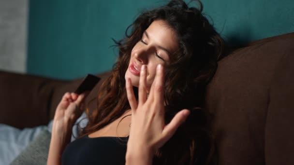 Sinnliches Mädchen leckt Finger mit Schokolade in der Hand. Sexy Frau isst Süßigkeiten.