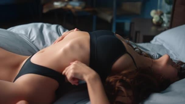 Sexy holka se prohýbá zpátky v posteli. Nahá žena kousání prst v moderní ložnici.