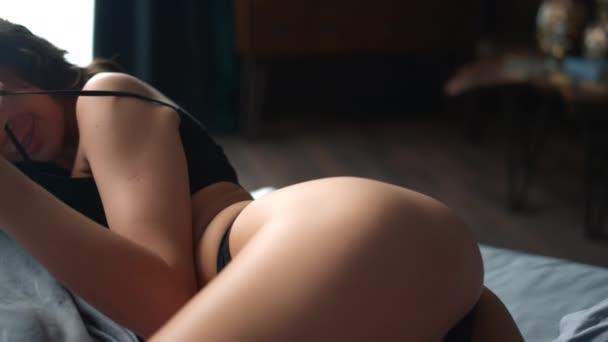 Perfektní tělo dívka usmívající se kamera v ložnici. Atraktivní žena ležící na břiše.