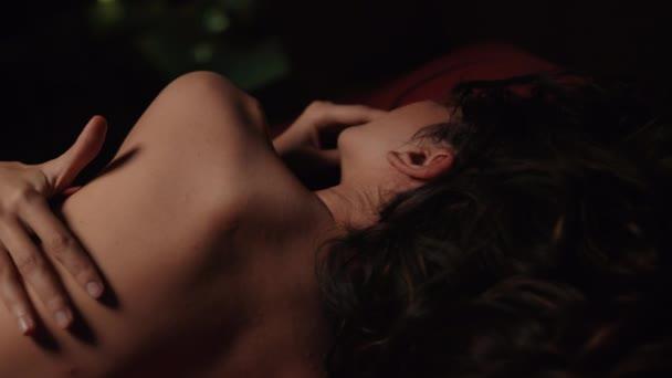 Nackte Mädchen, die rotes Seidenbetttuch bedecken. Junge Frau umarmt sich im Schlafzimmer.