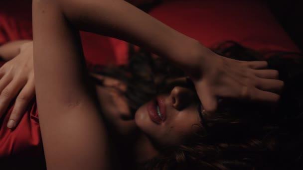 Szexi lány, vörös selyem lepedő alatt fekszik a hálószobában. Forró nő simogató nyak az ágyban.