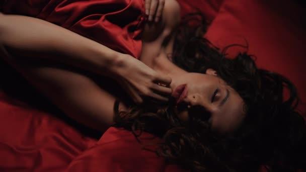 Szexductív nő, aki szexi ajkakat érint. Vonzó lány feküdt a piros selyem lepedő alatt