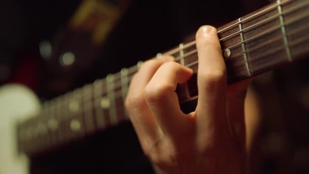 Kytarista hrající na akustickou kytaru ve studiu. Hudebník nacvičuje uvnitř.