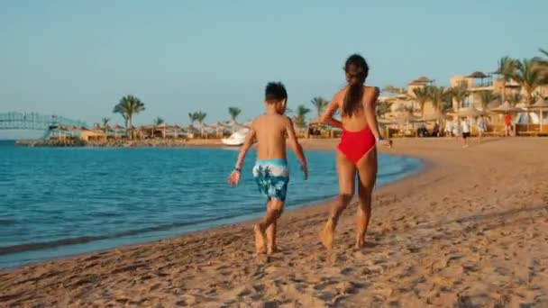 Barefoot children having fun at seashore in sunset. Sibling running on sea beach