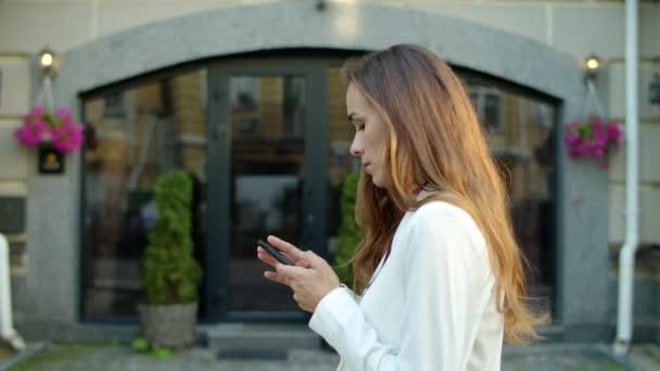 Obchodnice používá venku telefon. Hapyp žena dostává dobré zprávy venku