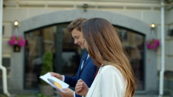 Úspěšný obchodní pár analyzující data v papírech společně venku